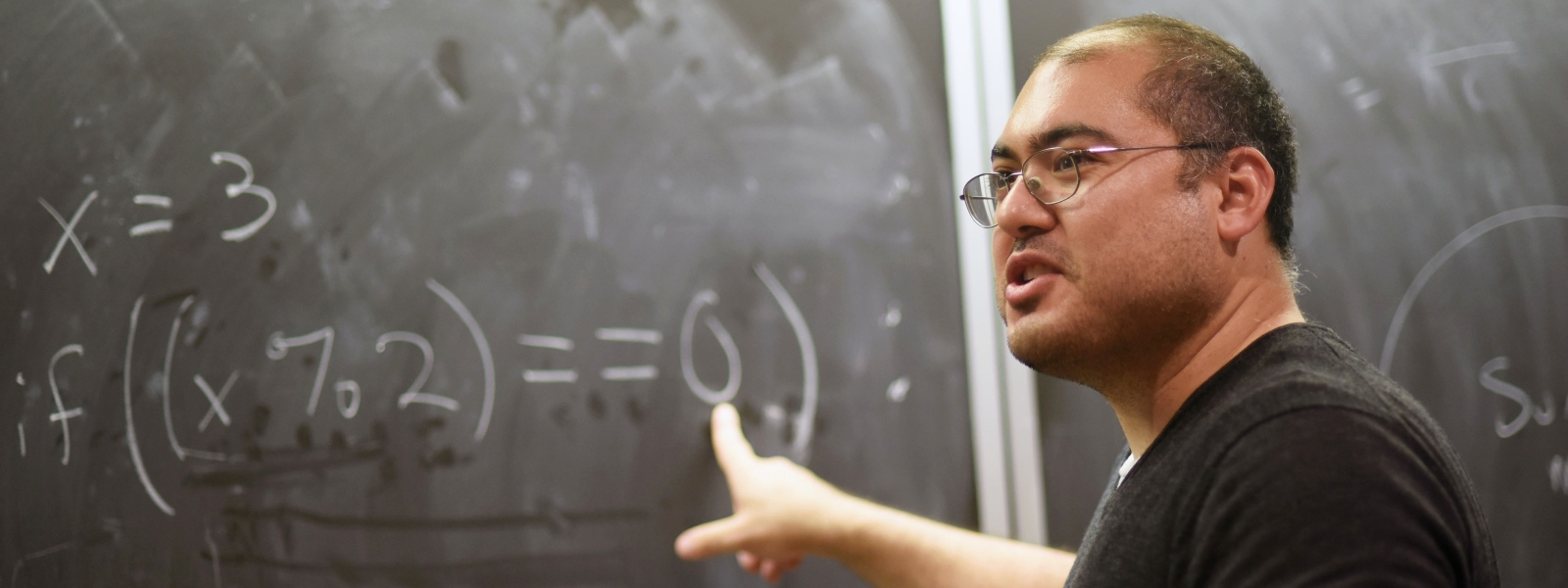 Math professor pointing to equations on the chalkboard